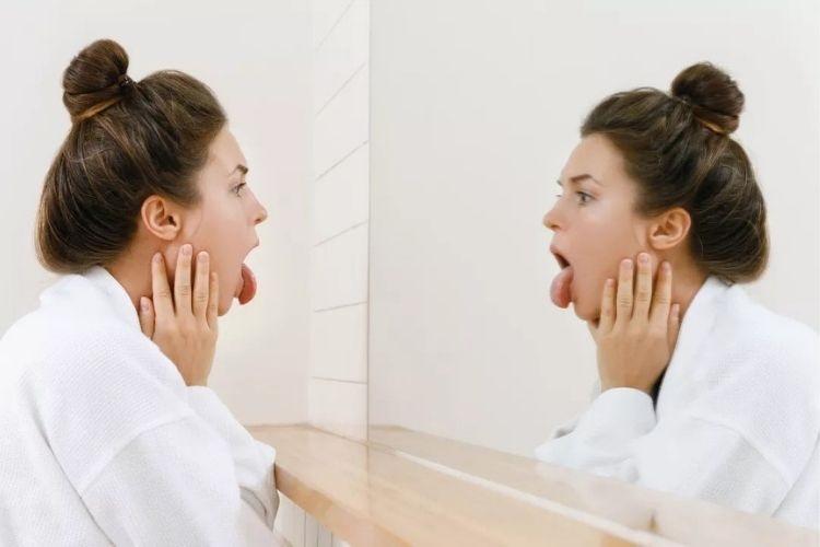mulher_ com_ a_ mão_ no_ rosto_ olhando_ para_ o_ espelho