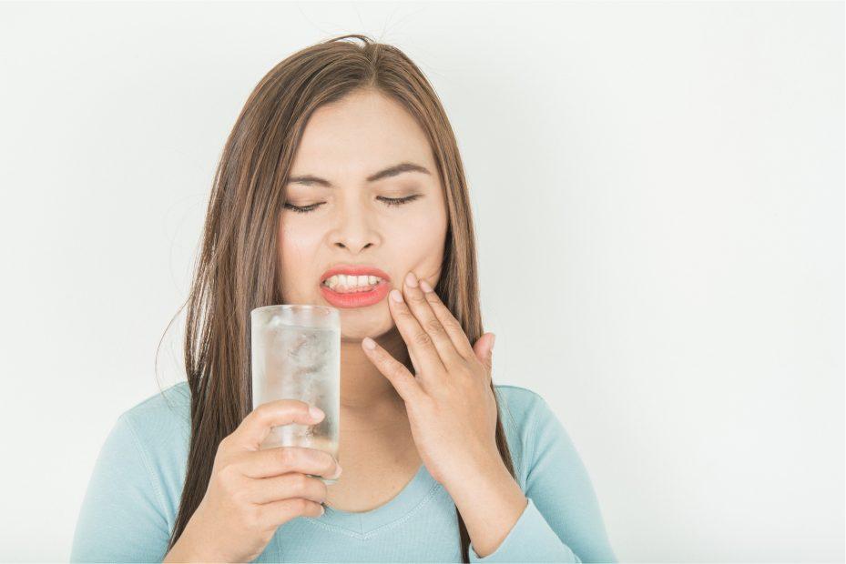 uma pessoa tomando água com dor nos dentes