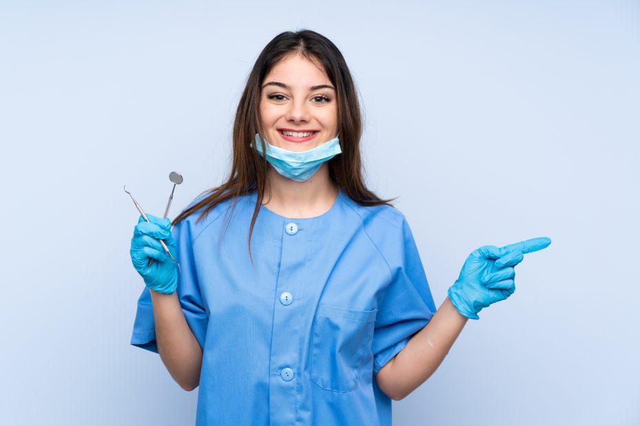 mulher-dentista-sorrindo-segurando-instrumentos